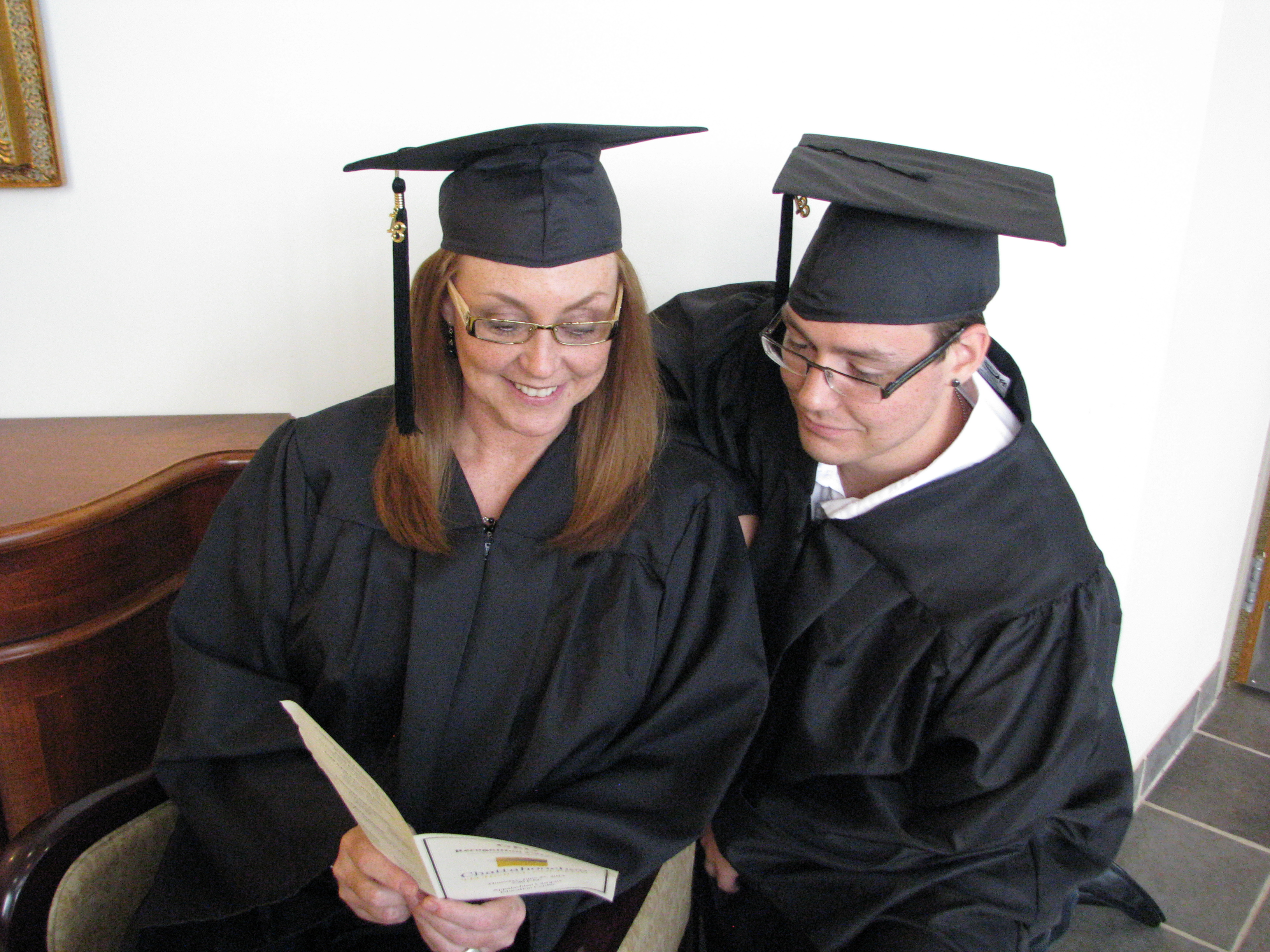 Male and female student in cap and gown