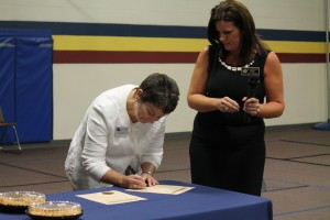 Dr. Trina Boteler signs the agreement as Jennifer Hernandez looks on during the school's PTSA meeting.
