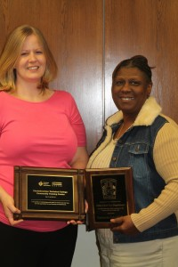 Shelby Martin and Robbi Thomas hold plaques given to Chattahoochee Technical College's American Heart Association Training Center for work in the community
