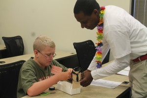 Engineering for Kids Camp Instructor Maurice Reid discusses the boat's design with Gavin Mosteller of Dallas.
