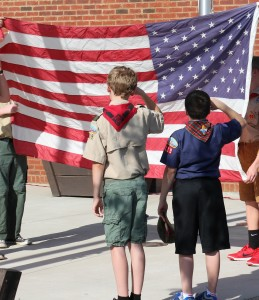 Members of Boy Scout Troop 119 salute the American flag.