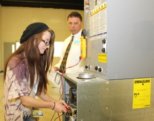 Air Conditioning Technology instructor Joe Esposito looks on as student Cheyanne Head gathers a reading from an AC unit in the AIRC lab.