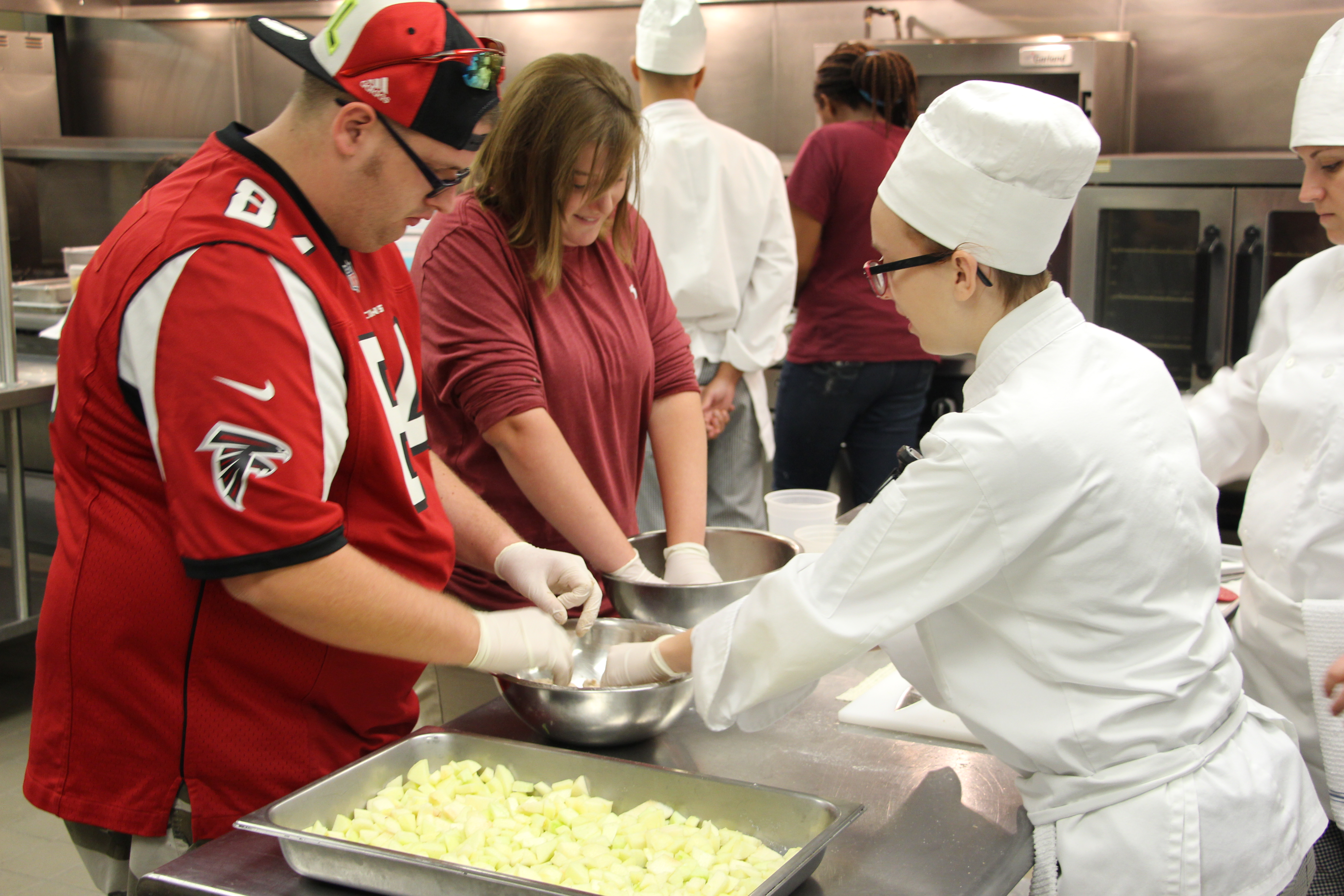 Photo of SETS students Carson Boyd and Madison Johnson building an apple crisp with the help of CTC Culinary Arts student Sara Sheets.