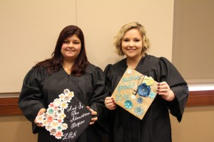 Woodstock resident Delaina Snarski and Powder Springs resident Brittany Thompson show off their graduation caps.