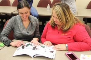 """Marietta resident Sarah Stiefler, on left, and Christy Albright of Kennesaw flip through a copy of """"Seeking Scruffy"""" during a book launch held Dec. 13 at the Mountain View Campus."""