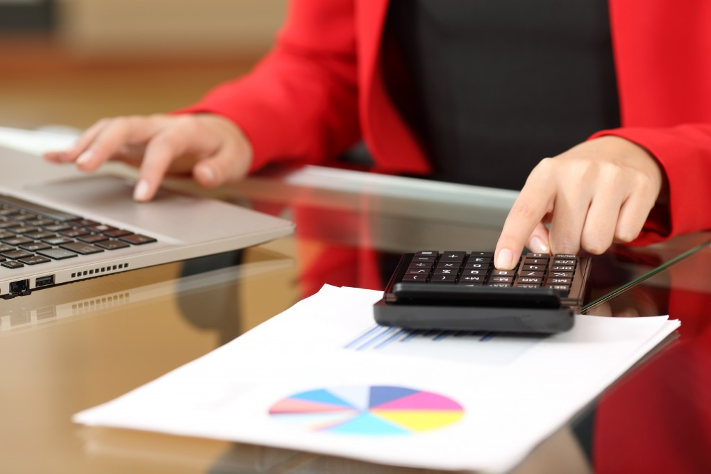 Closeup of a businesswoman hands accounting with a black calculator and a laptop sitting in a desktop at office with her red suit in the background