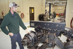 Photo of Diesel Equipment Technology instructor Evan Dover looking over a piece of training equipment.