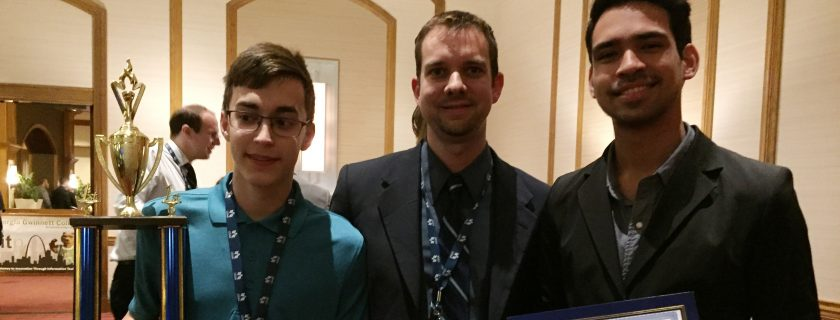 Two male students holding awards stand with club advisor at conference