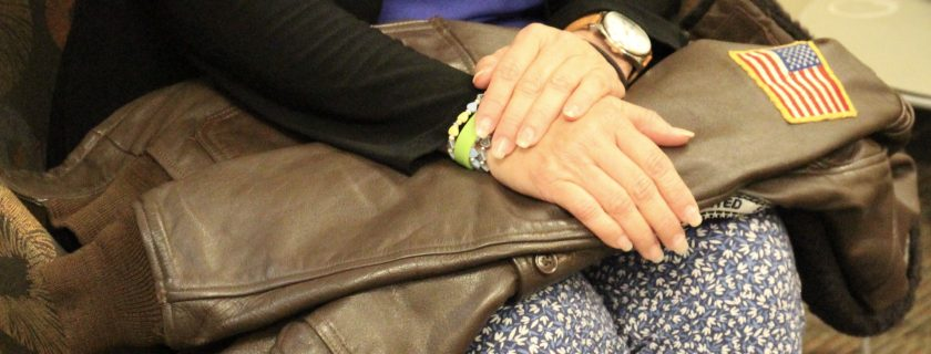 Woman's hands laid across a Navy jacket