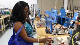 is Dr. Regina Hagood, head counselor at DeKalb High School of Technology South, examining a module used in the Industrial Maintenance and Electrical Technology lab