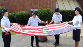 Members of The Bartow-Etowah Civil Air Patrol Composite Squadron 129. From left, Ryan Drawver and Jonathan Dicara hold the flag while Weston Walden cuts the stripes. Pictured, far right, is Olivia Adams.