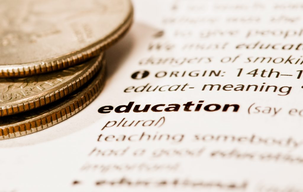 """A document with the word """"education"""" in bold type has a pile of US coins on it. Education can be expensive!"""