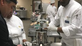 Chef Geybrayel, left, demonstrates part of the sausage making process as Stacey Dillard and Simon Stanley look on. The sausages will be featured at the college's upcoming Grand Buffet on Aug. 2.