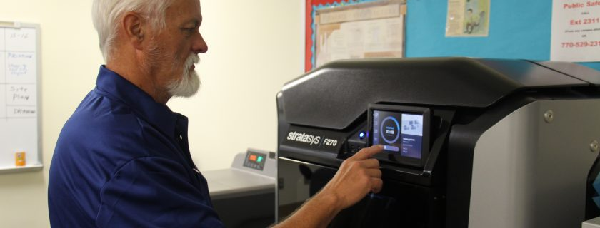 Photo of Drafting Technology instructor Jack Reece setting the Stratasys F270 printer for a new print job.