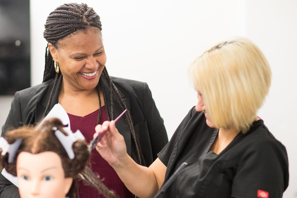 Cosmetology instructor smiling at student
