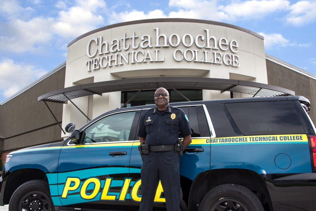 Chief Al Campbell in front of CTC police car at front entrance of North Metro campus