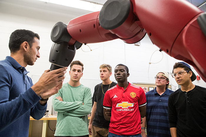 Industrial Maintenance students looking at robot