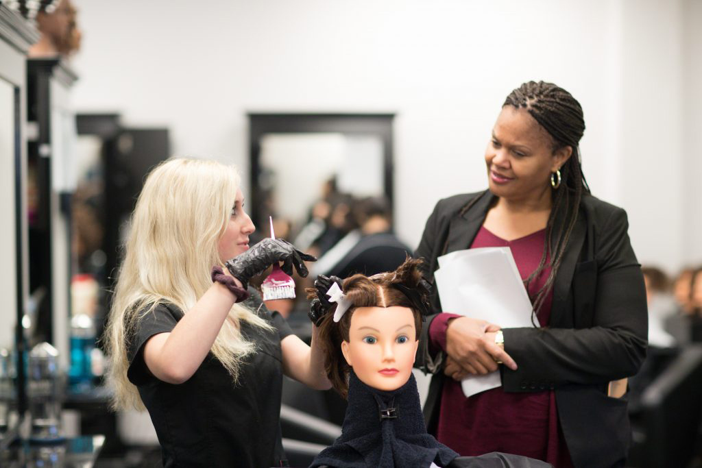Cosmetology instructor watching student style a wig