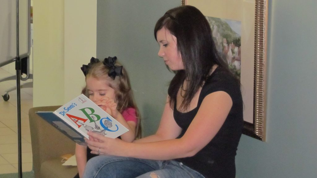 Woman reading to little girl