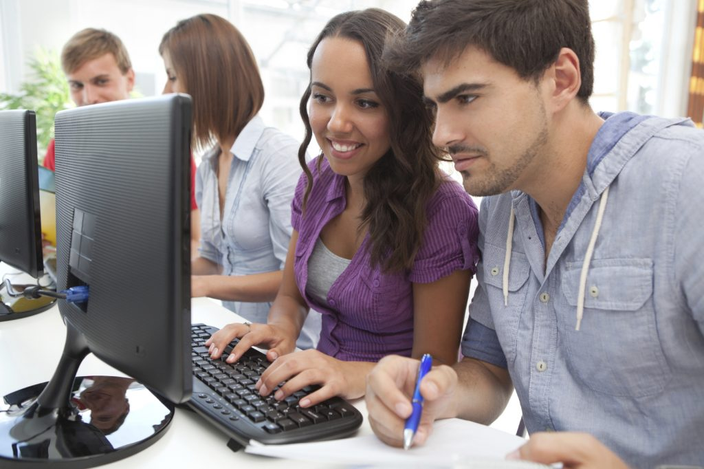 Male and female students working at computer.