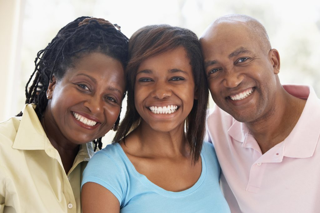 Couple With Their Teenage Daughter Smiling at Camera