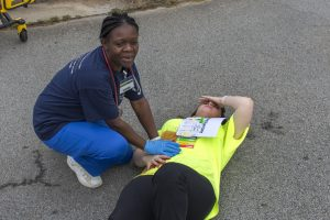 Photo of a student applying pressure to the mock wound of another student.