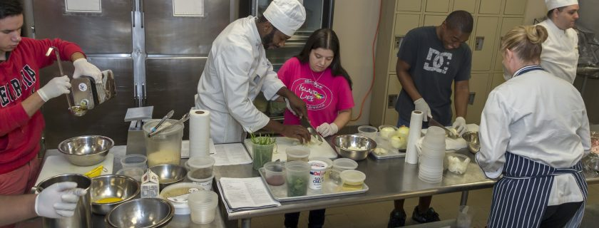 Photo of Chef Gallagher and CTC culinary students working with SETS students.
