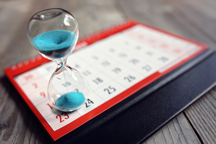 Hourglass and calendar on desk