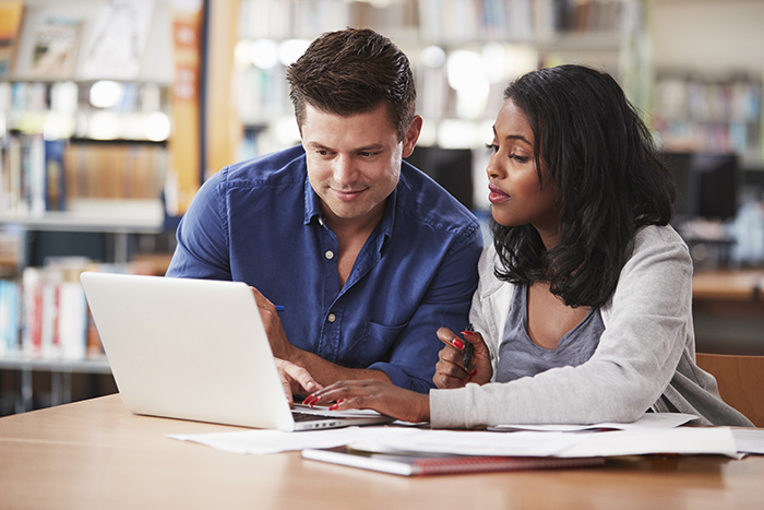 Male and female student in front of laptop