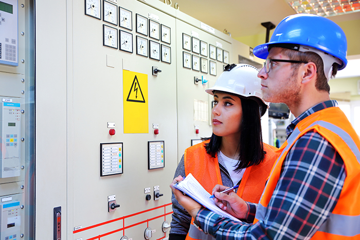 male and female electricians looking at panel