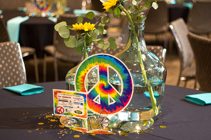 Colorful peace sign, flowers, and list of sponsors on table at Reverse Raffle 2018
