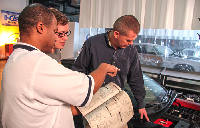 Teacher and two students in an Automotive Collision lab