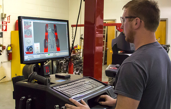 Automotive Tech in front of computer screen that displays a car graphic