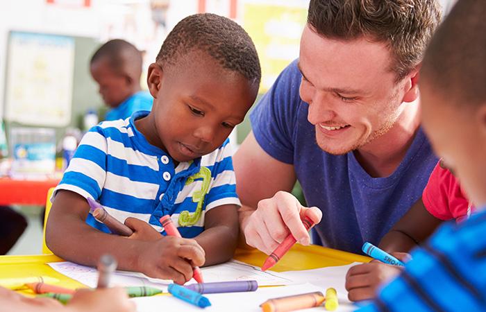 Male teacher drawing with preschool boys