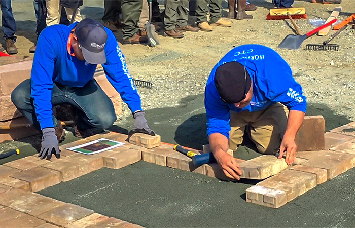 Horticulture students laying bricks on ground