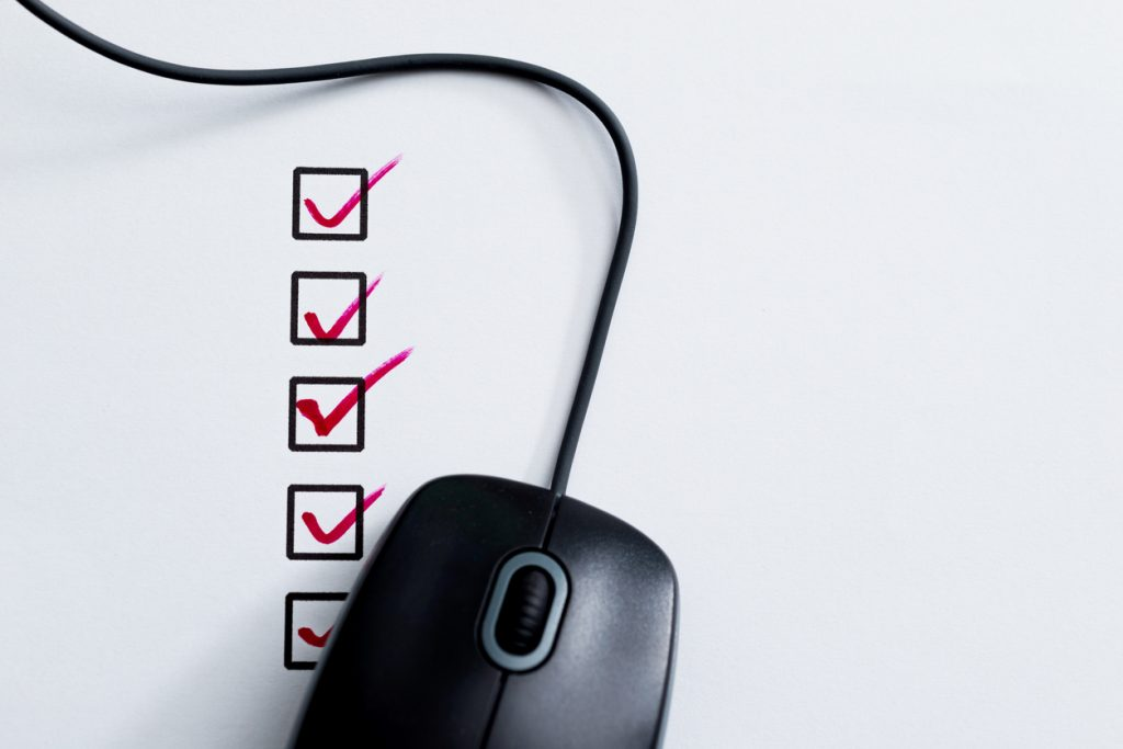 Computer mouse on top of checklist with checkboxes.