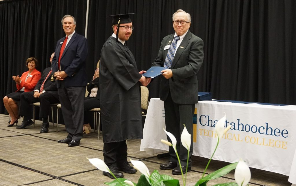 Chattahoochee Tech Biomedical Technology Adjunct Instructor Dr. Mike O'Rear presents his grandson, Dylan Claude Farist, with a certificate of achievement for earning his GED diploma.