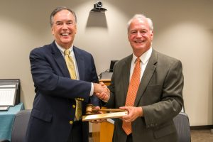 Board Chairman Mark Haney passes the gavel to incoming Board Chairman Steve Holcomb.