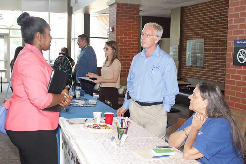 Men and women talking at Business and Technology Job Fair