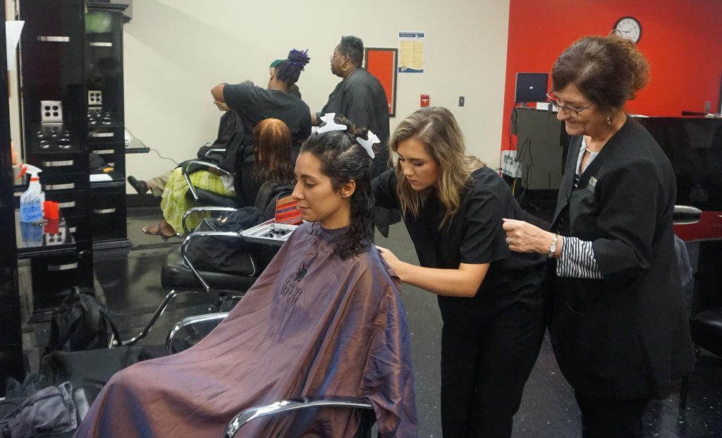 Cosmetology student Marci Holcomb is cutting hair for her first client ever, Rebecca Cardoso, at the Cosmetology program's salon on the North Metro Campus. Shown, l-r, are Cardoso, Holcomb and Instructor Colette Arp.