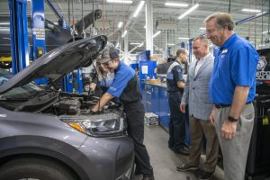 General Managers watch as CTC interns work on vehicle.