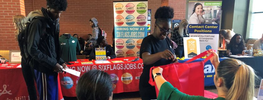 Students smiling at career fair tables