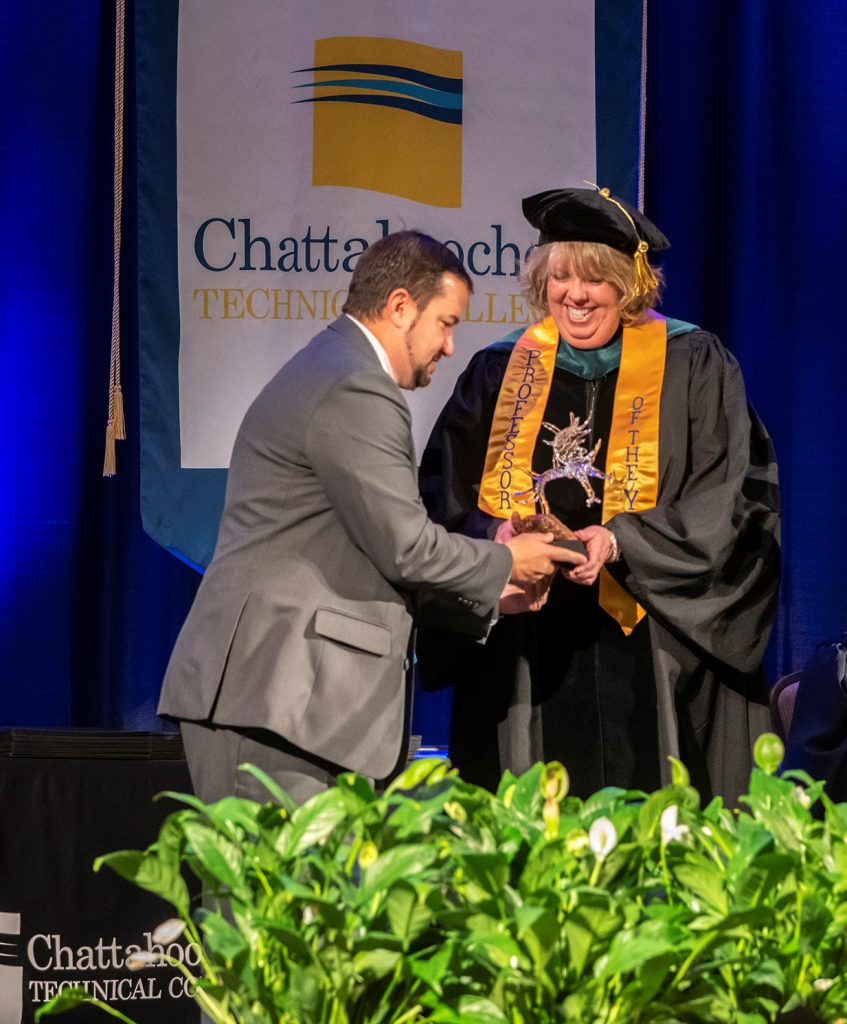 Chattahoochee Tech Foundation Board of Trustees Chairman Jason Anavitarte presents an award to PTA Program Director Stephanie Puffer, who is the college's 2019 Rick Perkins Instructor of the Year.