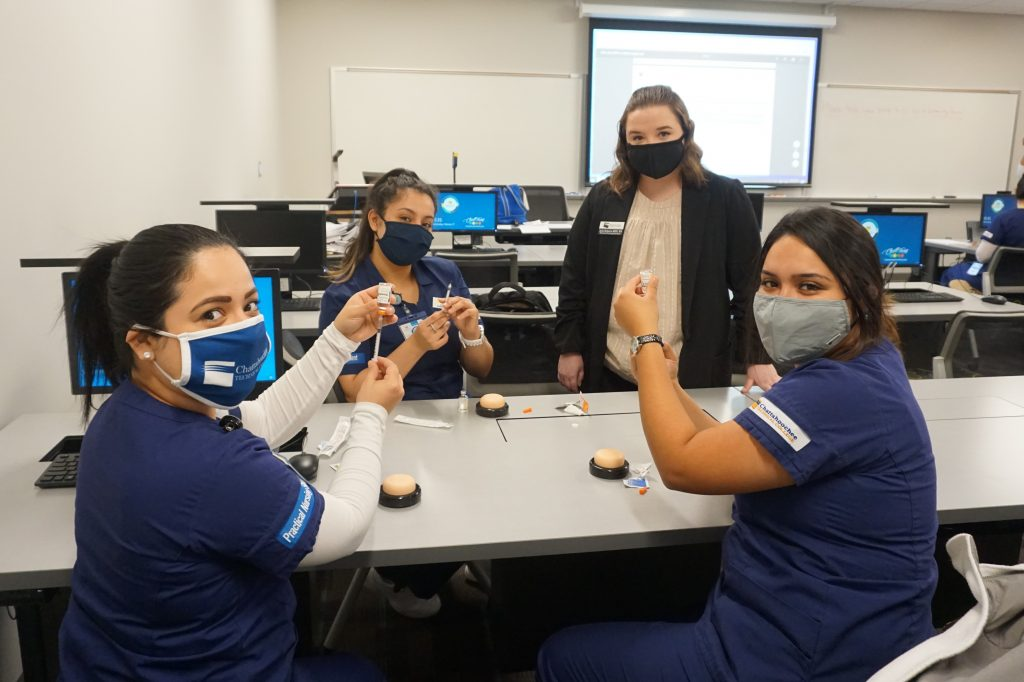 Shown here, l-r, with CTC Nursing Instructor Ayla Roberts, who is standing, are students Bianca Pineda, Yesica Patino, and Darlin Reyes-Cruz.