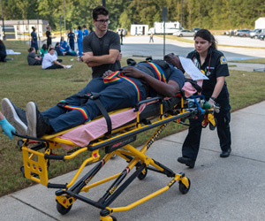Emergency Medical students practicing moving a patient