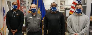 Four men wearing facemasks in front of flags