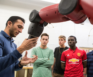 Instructor and three men with a robot