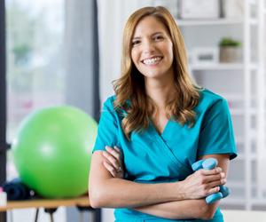 A smiling woman with a medicine ball