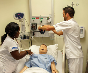 Two nurses practicing on a mock patient